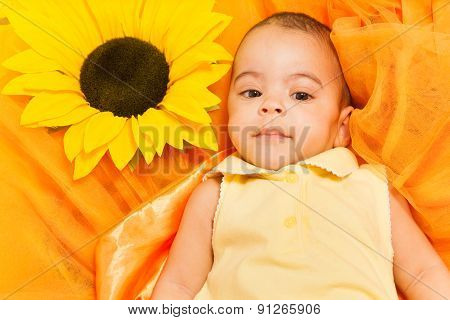 Portrait of African baby laying on sunflower cloth