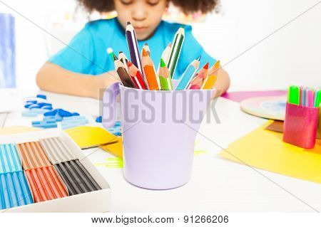 Close-up view of pencils and African girl writing