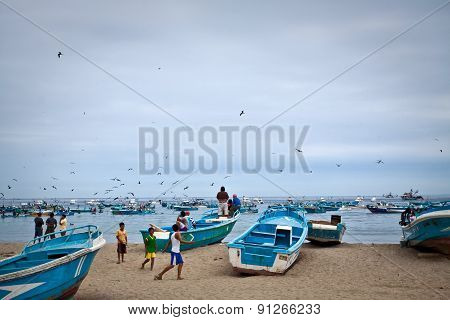 Busy fishermen in the morning along a beach shore, Puerto Lopez, Ecuador