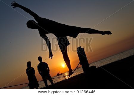 Silhouette of young man balancing on slackline at a beach in Manabi, Ecuador