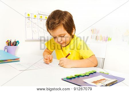 Concentrated small boy write with pencil alone