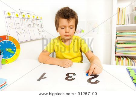 Boy learn to count put coins on the numbers