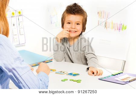 Smiling boy plays developing game with cards