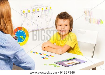 Smiling boy with colorful coins in order