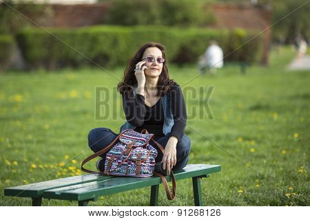 Young woman talking on the phone while sitting on the bench outdoors.