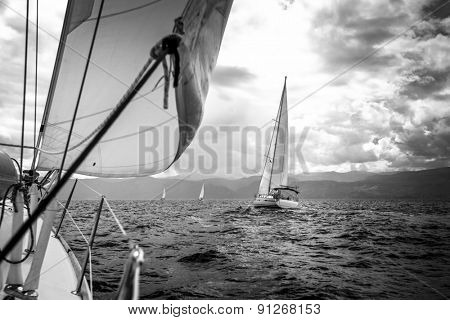 Sailing yachts in the sea in stormy weather. Black and white photo.