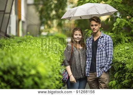 Young couple, boy and girl standing under an umbrella on the green track in the front yard near the house, looking at the camera.