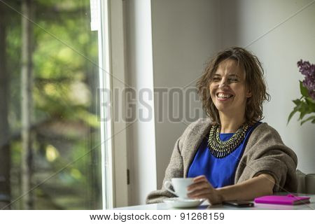 Young woman laughing while sitting near the window of his house.