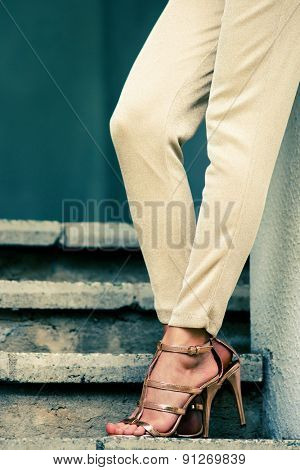 woman legs in high heel golden sandals stand on stairs, outdoor shot