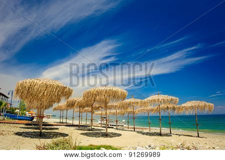 Rows of reed umbrellas on the sea beach