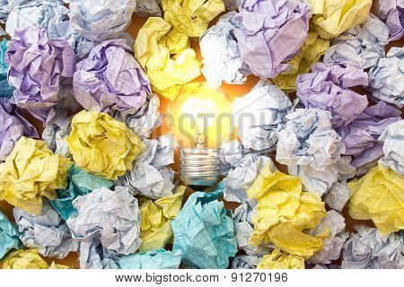 Burning Light Bulb Among Crumpled Paper Sheets