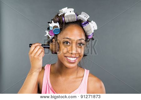 An African American woman putting on makeup