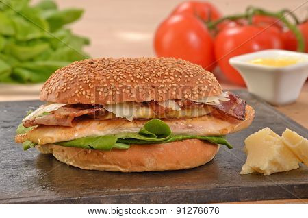 Chicken burger on grill stone and ingredients.