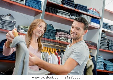 Couple shopping, man looking at price tag