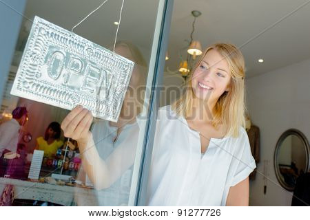 Woman with open shop sign