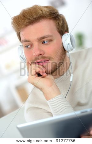 Surfing the net whilst listening to music through his headphones