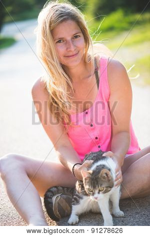 Young blonde woman playing with cat outdoor