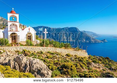 Iconic church with red roof on cliff, Greece
