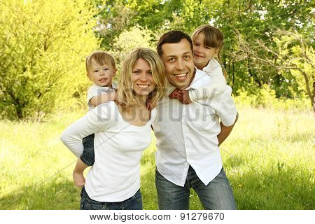Young Beautiful Family With Children In Nature