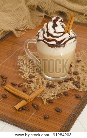 Iced Coffee With Foam And Cinnamon On Canvas And Wood