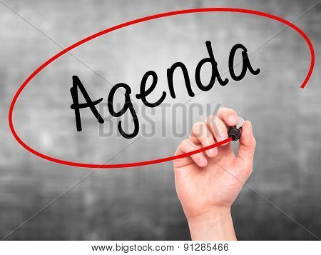 Man Hand writing Agenda with marker on transparent wipe board.
