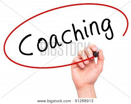 Man Hand writing Coaching with marker on transparent wipe board.