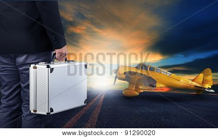 Business Man With Metal Strong Luggage Standing In Airport Runways With Yellow Old Yellow Propeller