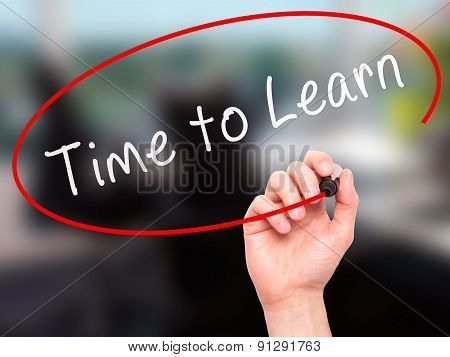 Man Hand writing Time to Learn with marker on transparent wipe board.