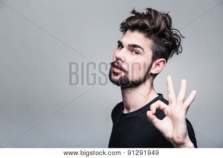 Young man in  black T-shirt shows gesture ok