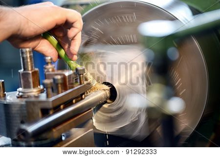 Man Placing Lubricating Oil On A Lathe