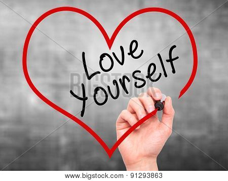 Man Hand writing Love Yourself with marker on transparent wipe board, inside heart shape.