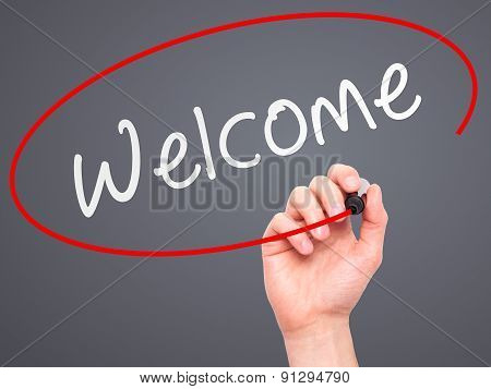 Man Hand writing Welcome with marker on transparent wipe board.