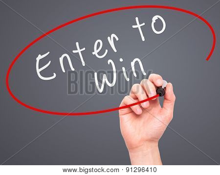 Man Hand writing Enter to Win with marker on transparent wipe board.