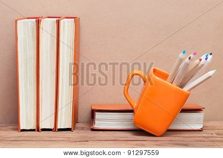 A Stack Of Books And A Mug With Colored Pencils On Wooden Table
