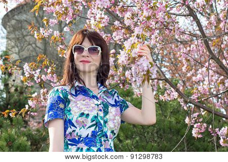 Portrait Of Attractive Woman Posing With Sakura Flowers In Park