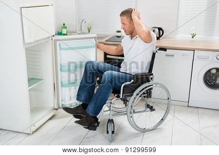 Disabled Man Looking In Empty Refrigerator