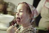 picture of cake-mixer  - Little girl licking chocolate off the mixer beater after mixing dough for birthday cake - JPG