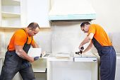 foto of carpenter  - Craftsman kitchen carpenter workers at kitchen furniture set installation service work - JPG