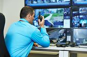 stock photo of cctv  - security guard watching video monitoring surveillance security system - JPG