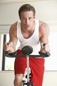 stock photo of exercise bike  - Young Man On Exercise Bike - JPG