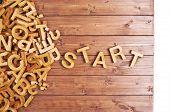 pic of start over  - Word start made with block wooden letters next to a pile of other letters over the wooden board surface composition - JPG