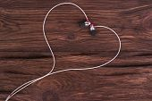 picture of heart sounds  - Heart of white headphones on a brown wooden background symbolizing love - JPG