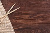 picture of chopsticks  - Chopsticks and bamboo napkin on a wooden brown background - JPG