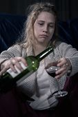 foto of alcohol abuse  - Portrait of young female alcoholic pouring wine - JPG