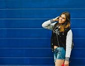 pic of rap-girl  - Happy young girl listening music  in headphones over blue wall background - JPG