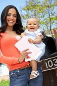 foto of mailbox  - Hispanic Mother And Baby Checking Mailbox - JPG