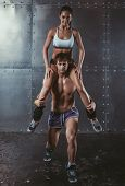 picture of squatting  - Athlete muscular sportsman doing exercising squats with woman sitting on his shoulders Crossfit fitness sport training lifestyle bodybuilding concept - JPG
