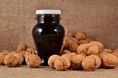 stock photo of walnut  - Jam from walnuts in glass jar and walnuts - JPG