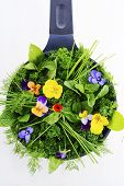 foto of edible  - Cooking with herbs concept with fresh herbs and edible flowers in modern yellow fry pan skillet on white wood table - JPG