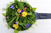 image of edible  - Cooking with herbs concept with fresh herbs and edible flowers in modern yellow fry pan skillet on white wood table - JPG